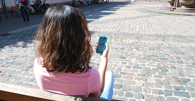 Woman sitting on a bench and holding a smartphone (Foto. Stadt Heidelberg)